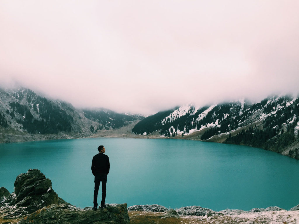 Photo of a man standing on a mountain near lake
