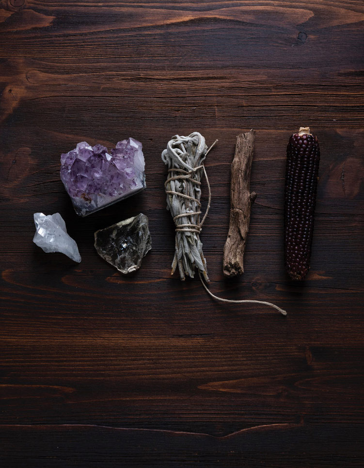Crystals and sage on a wooden surface