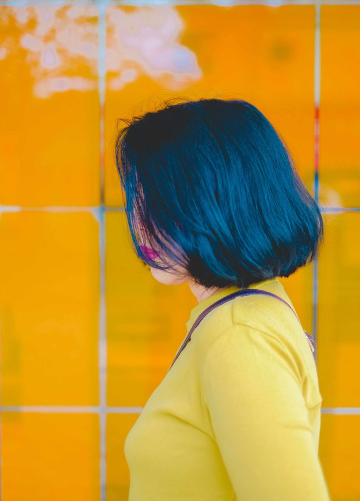 Photo of a woman with teal hair wearing a yellow shirt.
