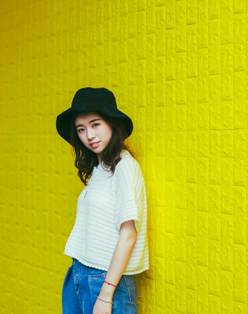 Photo of a woman leaning against a yellow wall.