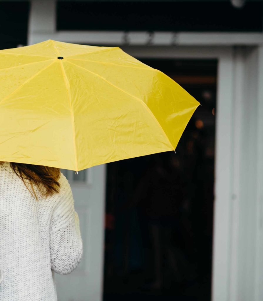 Photo of a woman holding a yellow umbrella.